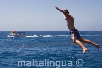Un étudiant faisant un saut étoile depuis le bateau