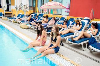 2 étudiants avec les jambes dans la piscine de la résidence