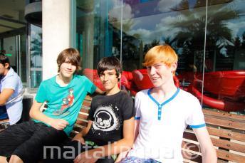 3 étudiants assis sur un banc en dehors de la résidence de l'école