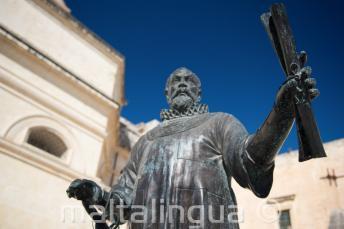 Une statue à Malte d'un homme tenant un parchemin