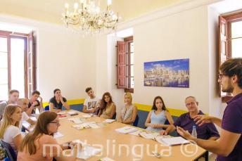 Étudiants écoutent l'enseignant dans une classe de langue anglaise
