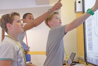 Un enseignant aidant 2 étudiants au tableau interactif