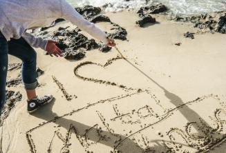 Étudiant écrivant I LOVE Maltalingua dans le sable