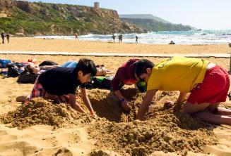 Chef de groupe et étudiants faisant un trou dans le sable à la plage
