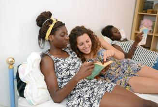 Un étudiant lisant un livre avec un membre de la famille d'accueil