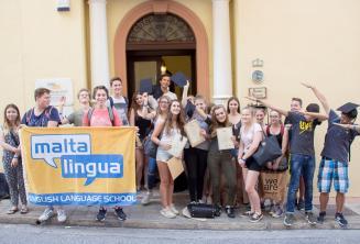 Groupe d'étudiants d'anglais ados à la porte principale de l'école